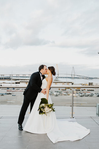 Bride and Groom kissing on the rooftop of the Cedar Room Wedding Venue over looking the Ravenel Bridge.