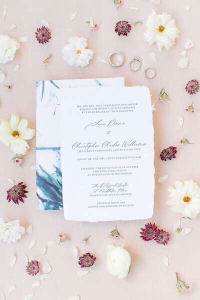 Deckle edge wedding invitation on ivory paper with indigo lettering alongside a vellum envelope featuring indigo watercolor illustrations