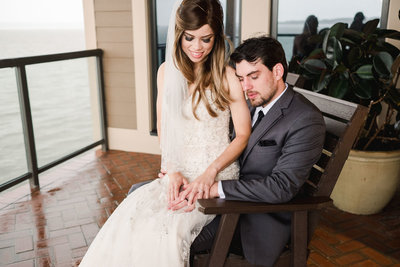 Bride sits on grooms lap in a wooden chair while they lovingly stare at their wedding rings