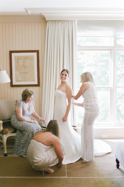 Bride smiling at camera while three women help her dress