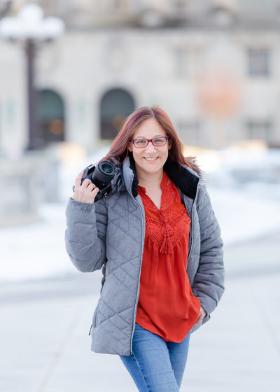 Lisa Han holding camera in a winter coat