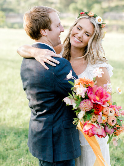 bride and groom with pink and orange bouquet
