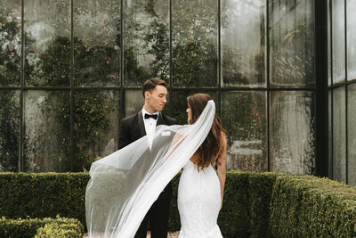 Bride and groom posed on wedding day in front of a botanical garden with a veil