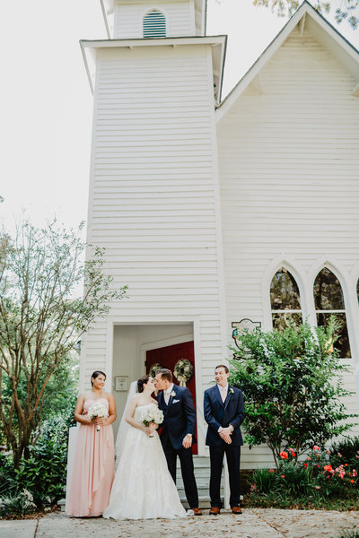 Bride and Groom kiss standing in front of church in Magnolia spring alabama with bridal party