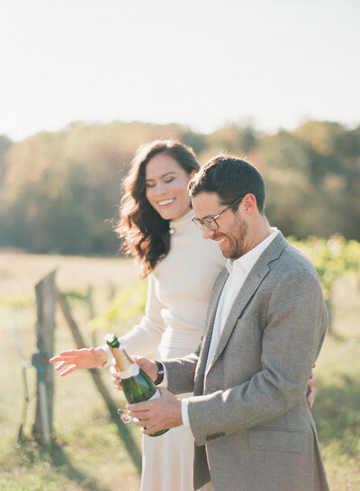 Engaged couple opens bottle of champagne during engagement portrait session