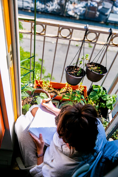 woman sits on her apartment balcony journaling