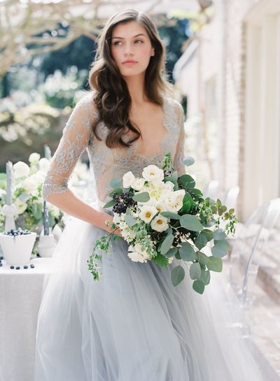 Bride with beautiful white bouquet of flowers in a lace, pale blue wedding dress