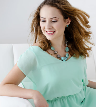 Portrait photograph of  beautiful teenager  with hair  blowing in teh air , wearing  aqua  blue  dress  and  costume jewellery necklace and  earings sitting on a couch. charming and  beautiful smiling face of the lady