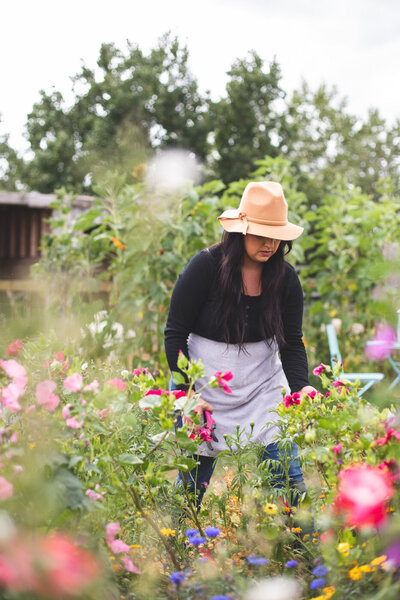 girl in a hat surrounded by pink flowers