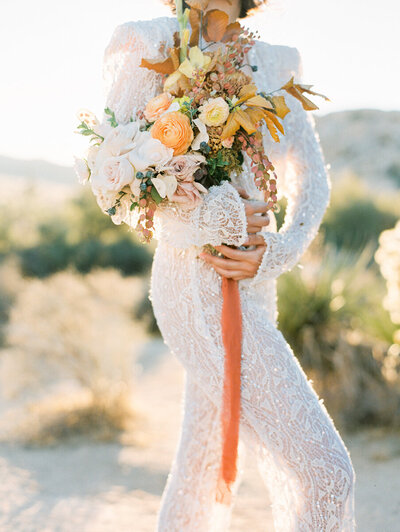 Bride stands in joshua tree desert wearing beaded long sleeve gown and oversize wedding bouquet with orange flowers at Joshua Tree National Park