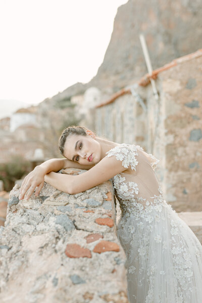Bride in stunning wedding dress leans against stone wall in Greece