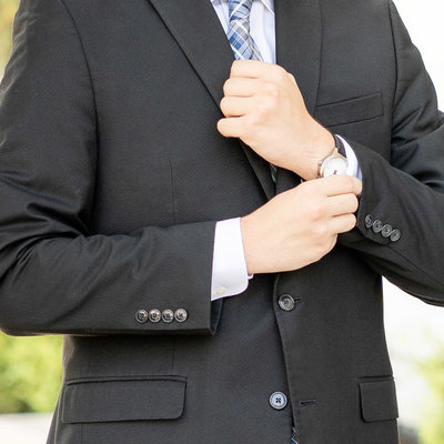 Wedding details Groom adjusting sleeve showing his round watch wearing a black jacket and blue tie