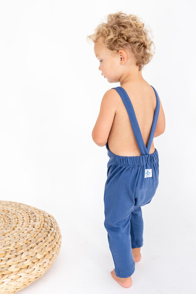 A toddler wearing a knitted blue romper