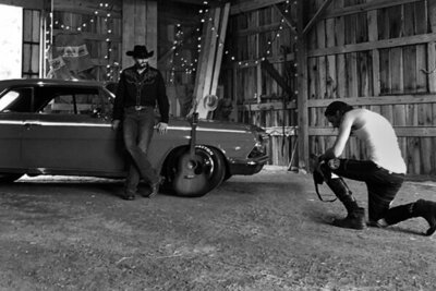Country Music Photography behind the scenes Mark Maryanovich kneeling while looking at back of camera Chance Moore standing next to vintage car inside barn with lights hanging from ceiling