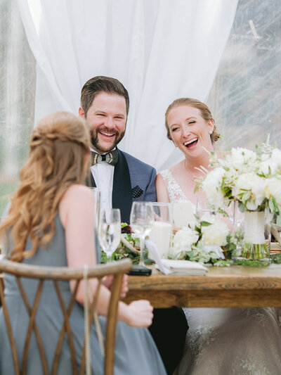 Bride and groom at reception table laugh happily with a wedding guest
