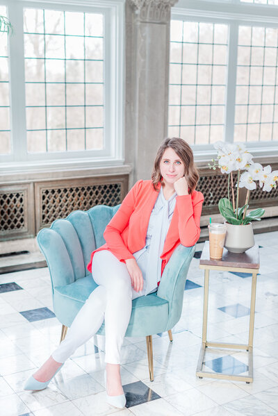 Woman looking at the camera sitting on a cram couch wearing a bright coral blazer