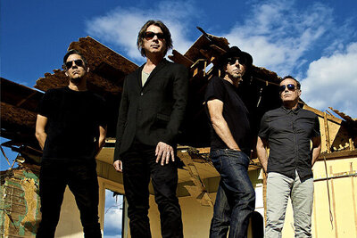 Band photo 5440 standing in front of dilapidated house blue sky and clouds above them