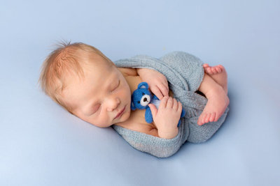 newborn boy swaddled in blue with teddy bear on blue background