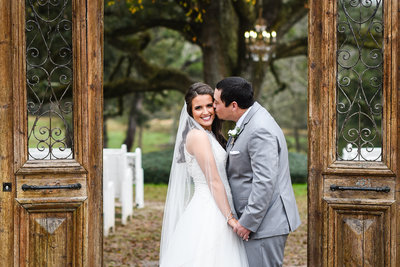 Bride and Groom kiss in front of live oak at The Venue at Southern Oaks Farm, Gulfport, MS, Mississippi Wedding