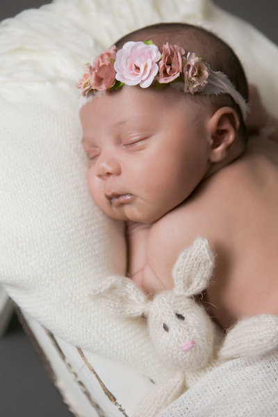 Infant with rose covered headband sleeping during the photoshoot.