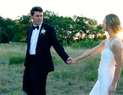 Groom and bride holding hands in field