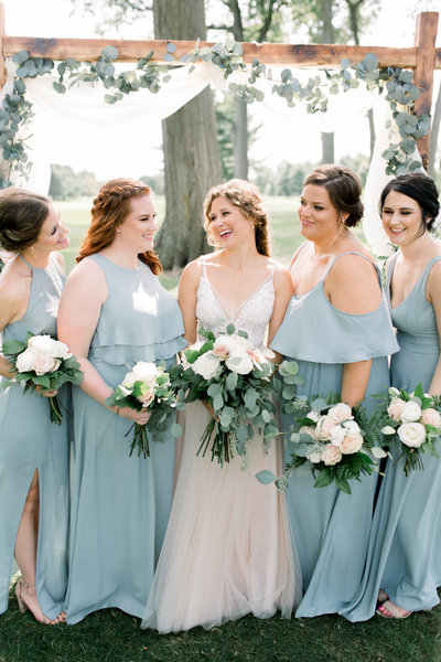 bride and bridesmaids laugh at Owosso Country Club wedding in Lansing Michigan photo by Cynthia Boyle wedding photographer in Grand Rapids