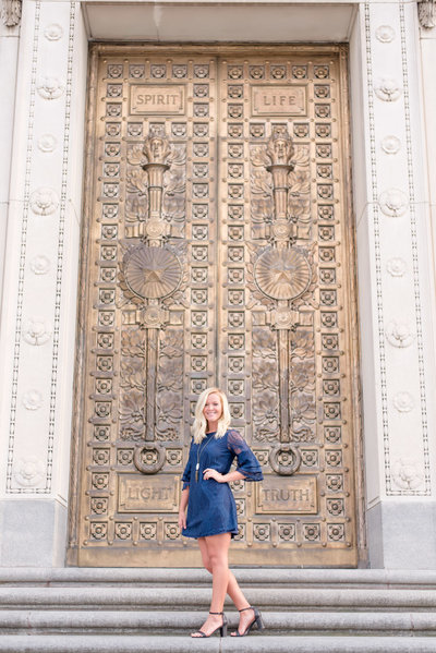 Senior stands in front of gold door.