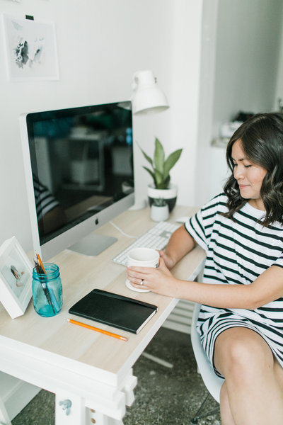 Designer with a cup of coffee at her desk