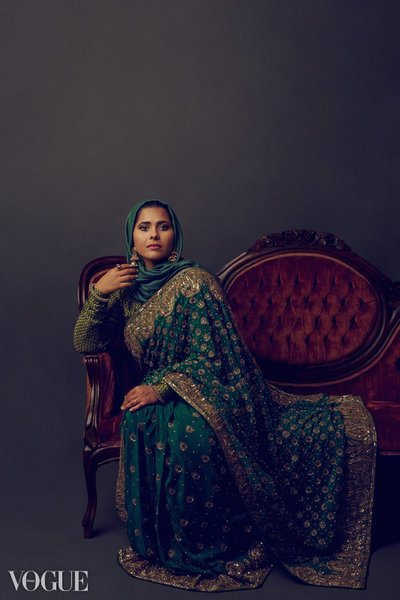 Woman in a sari sitting on an antique sofa.