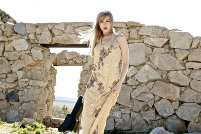female music photography Kendall Rucks standing against stone wall in desert wearing long beige dress