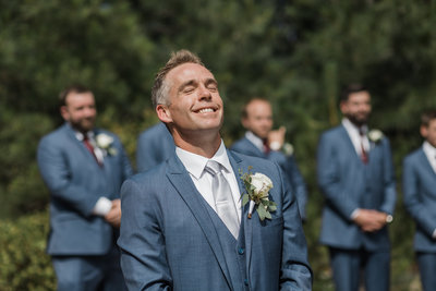 groom smiling with groomsmen in background