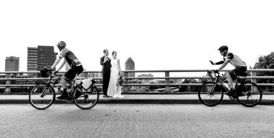 Cyclists wave at a bride and groom who are standing in front of the downtown Raleigh skyline on their wedding day