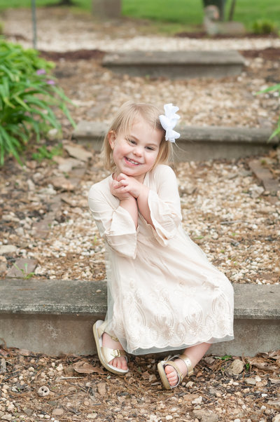 Adorable girl sitting on steps in garden in KY