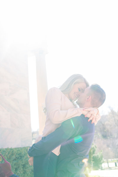 Sun flare engagement photo, couple hugging closely, Groom lifting Bride