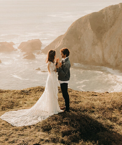 bride and groom standing next to ocean while looking at each other