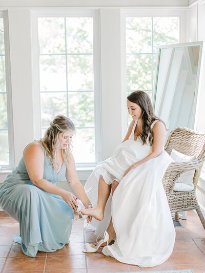 Bridesmaid helping bride put on shoes at Lexington Wedding..