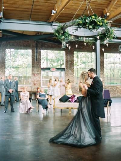 Victorian gothic bride and groom first dance photos  inside an industrial brick wedding venue in Atlanta