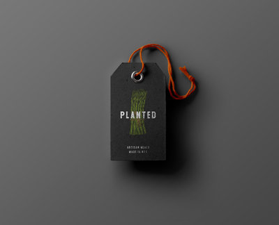 This is a dark grey shopping label with orange string for the brand Planted. The branding was done by Ile Alafia Design Co.