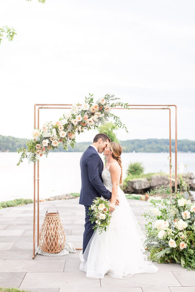 Photo of husband and wife kissing under ceremony arch at North Shore House wedding captured by NJ Wedding Photographer and NJ wedding videographer Diana & Korey Photo and Film