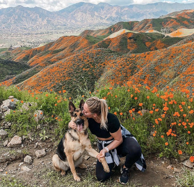 bree kissing sequoia during a hike in san diego