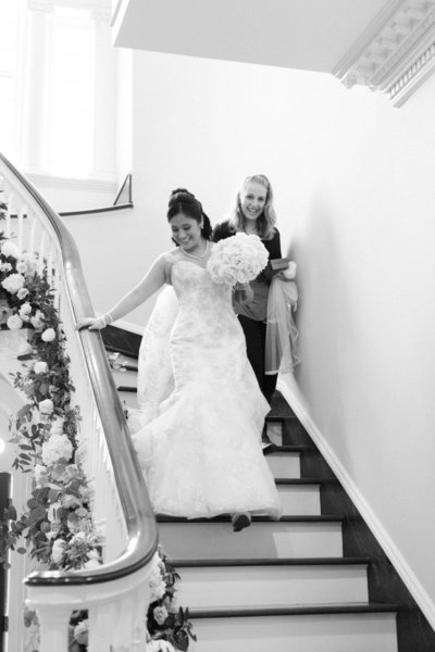 Tilly and Teal Wedding Planner helping Bride down the stairs at Great Marsh Estate