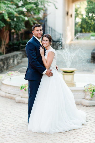Young dark haired man in navy suit embracing woman in white lace wedding down in front of a large water fountain