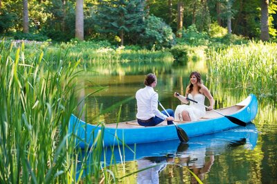 a bride and groom sit in a bright blue canoe on a sunny day at bridal veil lakes