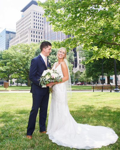 Bride and groom embrace in xyz park in Indianapolis after their wedding ceremony