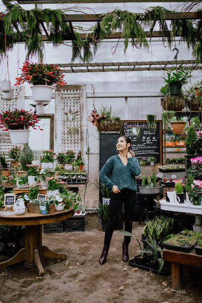 woman smiling surrounded by plants