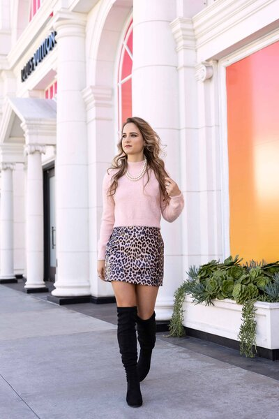 girl walking on the sidewalk in a  pink sweater and leopard print skirt
