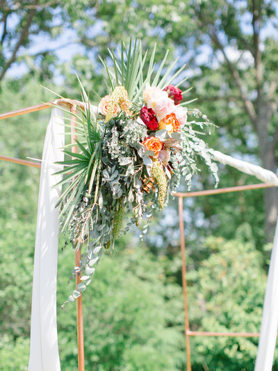 Outdoor wedding ceremony arch with corner flower arrangement