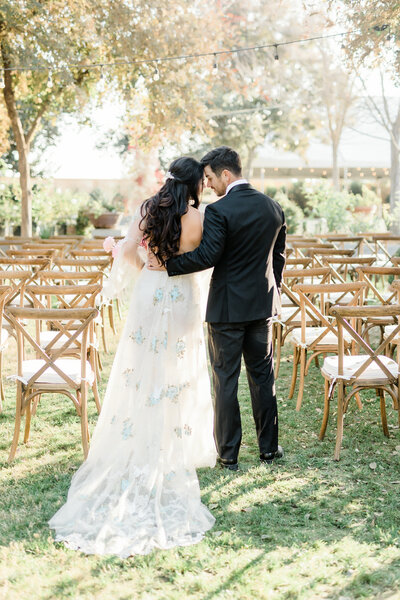 Los Angeles Wedding photographer Marianne Lucas wedding photo. Film photo, greenery bouquet, Oaks room, picture of a sweet heart table with glass surrounding the back of them. Calamigos Ranch Wedding Photographer