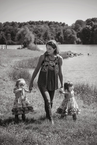 Image of Mother and twin daughters walking by a lake. Philadelphia