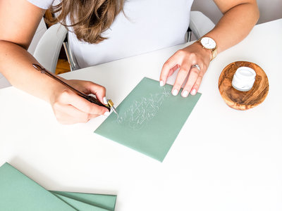 Pointed pen calligraphy with white ink on green envelopes